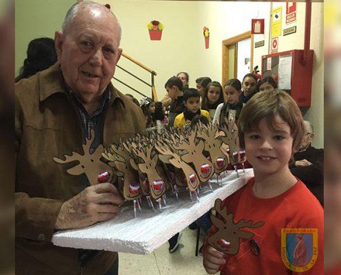 Abuelo de la residencia Virgen de Alharilla regala manualidad a niño visitante por Navidad